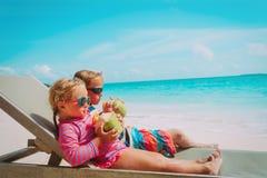 Coco de consumición del niño pequeño y de la muchacha el vacaciones de la playa foto de archivo libre de regalías