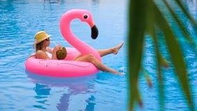 Coco de consumición hermoso de la mujer joven y relajación en un colchón inflable rosado en una piscina - modelo bonito con metrajes