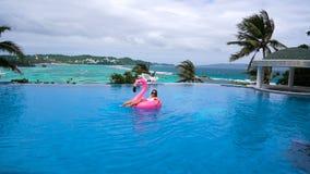 Coco de consumición hermoso de la mujer joven y relajación en un colchón inflable rosado en una piscina - modelo bonito con almacen de metraje de vídeo