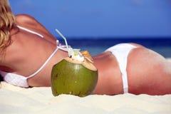 Coco en el fondo de la muchacha en la playa Fotografía de archivo libre de regalías