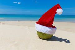 Coco en playa tropical de la arena del sombrero de Santa Christmas Foto de archivo