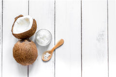 Coco fresco con aceite cosmético en tarro en la opinión superior del fondo blanco Fotos de archivo