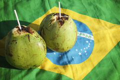 Coco Gelado Drinking Coconuts Brazilian Flag. Pair of coco gelado verde green drinking coconuts sitting in bright Brazilian sun on Brazil flag Royalty Free Stock Photo