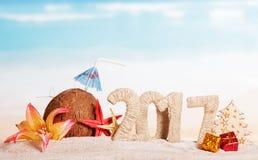 Coco, número 2017, estrellas de mar, flor, árbol y presentes contra el mar Imagen de archivo libre de regalías