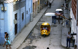 Coco Taxi moves down small street filled with people in Havana Stock Photos