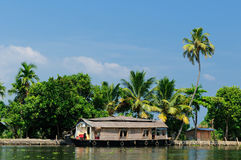 Coco trees reflection and beautifoull house boat stock photography