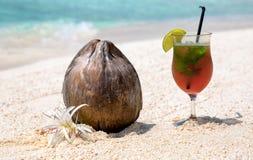 Coco y cóctel en una playa Foto de archivo
