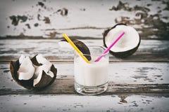 Coco y leche de coco en un vidrio Foto de archivo libre de regalías