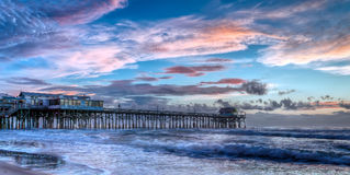 Cocoa Beach Pier at sunrise with blue and pink sky royalty free stock photography