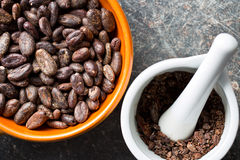 Cocoa beans in bowl and mortar Stock Photo