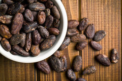 Cocoa beans in bowl on wooden table Stock Images
