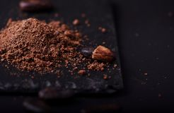 Cocoa beans and cacao powder on dark background royalty free stock photo