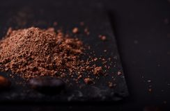 Cocoa beans and cacao powder on dark background. Closeup stock image