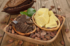 Cocoa beans, cocoa butter and cocoa mass. On brown background Royalty Free Stock Photos