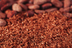 Cocoa beans and grated chocolate background, shallow dof Royalty Free Stock Photo