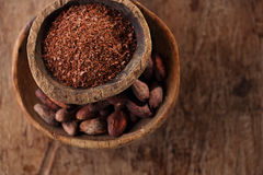 Cocoa beans and grated dark chocolate in old texured spoons bowl Stock Photo