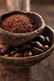 Cocoa beans and grated dark chocolate in old texured spoons bowl Stock Photos