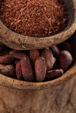 Cocoa beans and grated dark chocolate in old texured spoons bowl Royalty Free Stock Photos