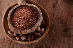 Cocoa beans and grated dark chocolate in old texured spoons bowl Stock Photography