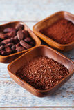 Cocoa beans, powder and grated chocolate in wooden bowls Royalty Free Stock Photography
