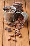 Cocoa beans in two tin buckets and dark chocolate Stock Photo