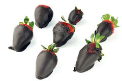 Cocoa and Berries. Seven chocolate candy coated strawberries on white Royalty Free Stock Photos