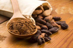 Cocoa (cacao) beans on natural wooden table Stock Photo