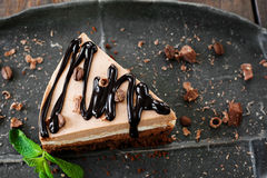 Cocoa cheesecake and chocolate sauce, black plate Stock Images