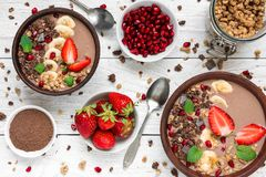 Cocoa or chocolate and banana protein smoothie bowls with granola, strawberry and pomegranate seeds served for breakfast. With spoons on white wooden table. top royalty free stock photo