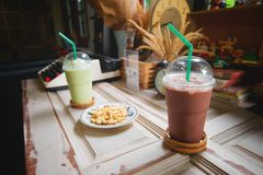 Cocoa, Chocolate and Green tea milk frappe in clear plastic glass have green straw and Alphabet cookies on wood shelf at cafe. Cocoa, Chocolate and Green tea royalty free stock images