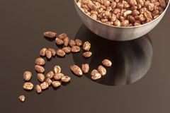 Cocoa coated puffed rice  in metal bowl. Cocoa coated puffed rice in metal bowl, cereal on black mirror Royalty Free Stock Image