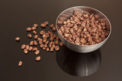 Cocoa coated puffed rice in metal bowl. Cereal on black mirror Stock Photo