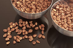 Cocoa coated puffed rice  in metal bowls. Cocoa coated puffed rice in metal bowls, cereal on black mirror Stock Image