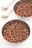 Cocoa coated puffed rice in metal bowls on white. Background Stock Image