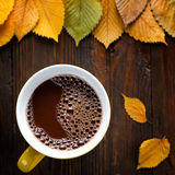 Cocoa drink. And autumn leaves on wood Stock Image