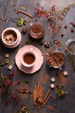 Cocoa drink with cinnamon, fresh cocoa powder, cane sugar on rustic wooden background, top view. Stock Photography