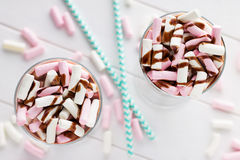 Cocoa drink with colorful marshmallows, chocolate topping and straws. Stock Photos