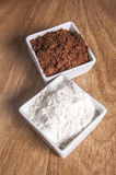 Cocoa and flour. Ingredients: flour, cocoa on a wooden background Royalty Free Stock Image