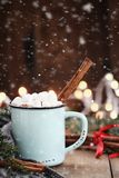 Cocoa with Marshmallows and Cinnamon Bark with Falling Snow Royalty Free Stock Photo