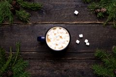 Cocoa with marshmallows on a wooden background with branches of spruce and pine cones winter theme royalty free stock image