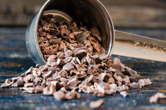 Cocoa Nibs. Spilled from measuring cup royalty free stock photography