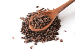 Cocoa Nibs into a spoon. Isolated on white background royalty free stock photo