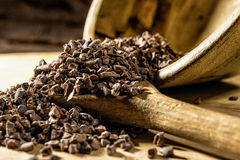 Cocoa nibs. On wooden spoon on a wooden board stock photos