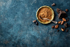 Cocoa powder, beans and dark chocolate pieces crushed, culinary background. Top view royalty free stock photo