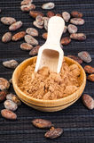 Cocoa powder in bowl with cacao beans around Stock Image