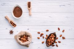 Cocoa powder and cacao beans on wooden background stock image