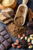 Cocoa powder, chocolate, nuts and spices. On a wooden table. Food photography royalty free stock photos