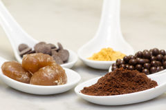 Cocoa powder, chocolate pralineand drop,  marron glacee and gold Royalty Free Stock Image