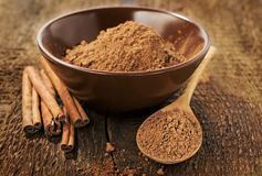 Cocoa powder and cinnamon sticks Royalty Free Stock Photos