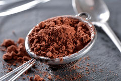 Cocoa powder close-up with sieve on black slate plate Royalty Free Stock Photo